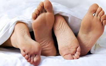 two pairs of feet between the sheets