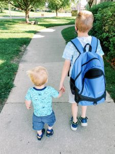 two little boys holding hands while walking