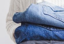 person holding two pairs of folded jeans