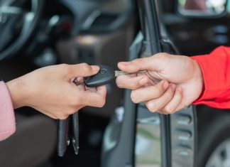 one person giving car keys to another, only hands pictured