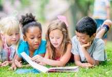 four young kids reading a book together
