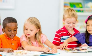 four kindergarteners reading books together