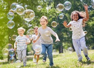 group of kids running through bubbles