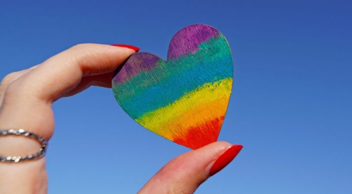 rainbow heart being held between thumb and pointer finger