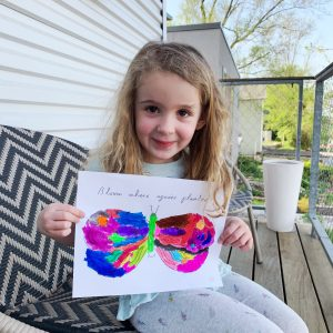 a little girl holding a butterfly she colored