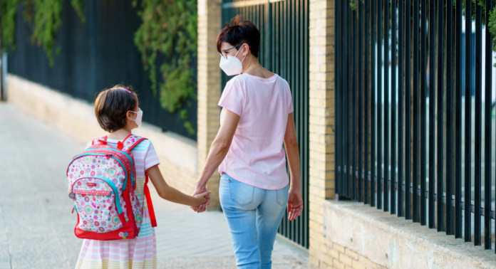 mom and daughter walking to school in masks