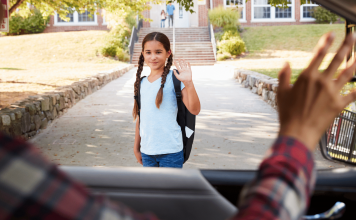 mom waving to girl outside school